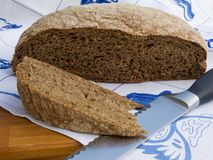 Freshly baked loaf of bread with a slice and cutting knife Royalty Free Stock Image