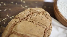 Freshly baked loaf of homemade organic sourdough rye bread on wooden table stock video