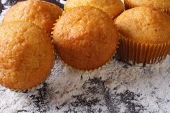 Freshly baked muffins orange macro and spilling flour,  top view Stock Photo
