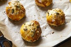 Mini brioche buns on the baking tray. Freshly baked multi seeded mini brioche buns on baking tray Royalty Free Stock Photos