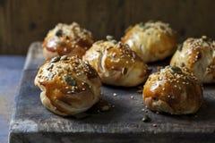 Mini brioche buns on the wooden board. Freshly baked multi seeded mini brioche buns on the wooden board Stock Image