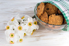 Freshly baked oatmeal raisin cookies and narcissus Royalty Free Stock Photography