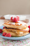 Freshly baked pancakes. Stack of delicious and fresh american pancakes topped with raspberries and maple syrup Royalty Free Stock Photo