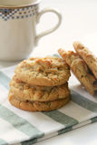 Freshly baked peanut butter cookies. On white plate with mug of tea in the background Stock Photo