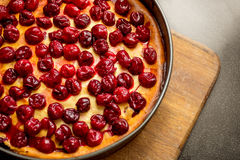 Freshly baked pie decorated by cherries on wooden board Stock Photos