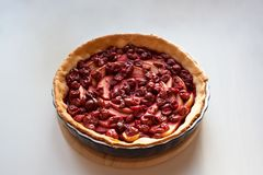 Freshly baked pie filled with sliced apples and cherries stock image