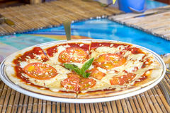 Freshly baked pizza with cheese and tomatoes served in small out Stock Photography