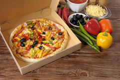 Pizza box, fresh pizza, ingredients, making pizza. Freshly baked Pizza in a delivery box surrounded by various ingredients on a wood table or worktop Stock Images