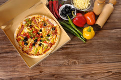 Pizza delivery box, ingredients, copy space. Freshly baked Pizza in a delivery box surrounded by various ingredients on a wood table or worktop Stock Photography