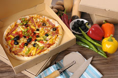 Freshly baked Pizza in delivery box with ingredients. Freshly baked Pizza in a delivery box surrounded by various ingredients on a wood table or worktop Stock Photo