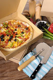 Freshly baked Pizza in delivery box with ingredients. Pizza box : freshly baked Pizza in a delivery box surrounded by various ingredients on a wood table or Stock Photography