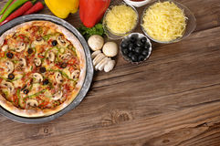 Pizza baking background, ingredients, copy space. Freshly baked Italian Pizza on a kitchen table surrounded by various ingredients and copyspace Stock Photography