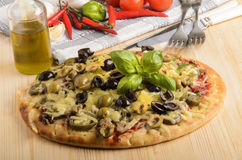 Freshly baked pizza with olive and melted cheese on a wooden boa Royalty Free Stock Photos