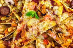 Freshly baked pizza with salami, mussels and shrimp, fried piece. S of close-up, garnished with fresh mint stock photo