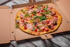 Freshly baked pizza. Spicy, meaty, cheese pizza in a carton box. Pizza on a gray background. Pizzeria delivery concept. stock photo