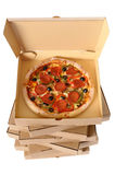 Freshly baked Pizza with stack of delivery boxes Royalty Free Stock Image