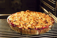 Freshly baked plum pie with almonds and crumble on top in the ov Stock Photo