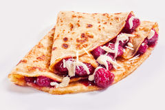 Freshly baked raspberry crepes or griddlecake. Freshly baked golden raspberry crepes or griddlecake drizzled with cream and folded in quarters ready to serve Stock Image