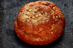 Freshly baked roll with ruddy crust and powder on a black textural background close-up. Rouge freshly baked bread with powder on a black textural background. The Stock Images