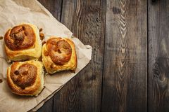 Freshly baked rolls with cinnamon with spices and raisins on parchment paper. View from above. Sweet homemade pastries. Close-up. Stock Image