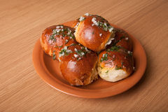 Freshly baked rolls lying in the ceramic dish on wooden table Royalty Free Stock Photography