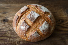 A freshly baked rustic, loaf of bread. On an old wooden table Stock Photo