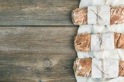 Freshly baked rustic  village bread (baguette) set on rough wood Stock Images