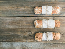 Freshly baked rustic  village bread (baguette) set on rough wood Royalty Free Stock Photography