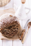 Freshly baked rye bread cob and kitchenware on wooden background Stock Images