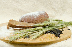 Freshly baked rye bread. On a wooden board with ears of wheat, flour, grains and seeds stock images