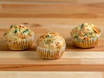 Freshly baked savoury muffins with cheddar, spinach and bell pepper. Freshly baked savory muffins with cheddar, spinach and bell pepper placed on a wooden board Stock Photography