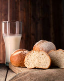 Freshly baked sliced buns and glass of milk Stock Images