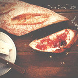 Freshly baked and sliced French baguette with strawberry jam on Stock Photo