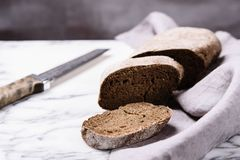 Freshly baked sliced rye bread and knife on linen napkin on marble table royalty free stock images