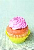 Freshly baked strawberry and vanilla cupcake. On green background Stock Image