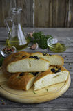 Freshly baked traditional Italian focaccia bread with rosemary and black olives on wooden background Royalty Free Stock Photography