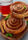 Freshly Baked Traditional Sweet Cinnamon Rolls, Swirl with hot black Tea and mint Stock Photography