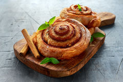 Freshly Baked Traditional Sweet Cinnamon Rolls, Swirl on wooden board Stock Photo