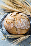 Freshly baked traditional wheat bread and wheat ears Royalty Free Stock Image