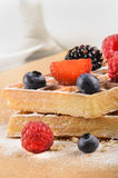 Freshly baked waffles with sweet fruits and powdered sugar. Freshly baked waffles with sweet fruits, blueberry, strawberry, blackberry, raspberry and powdered Stock Photos