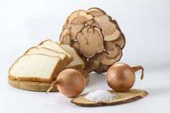 Freshly baked white bread with onion salt and wheat ears. Freshly baked bread on a stand with salt and onions with wheat ears Stock Image