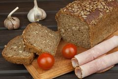 Freshly baked whole wheat bread. Preparing homemade breakfast. Various ingredients for the meal. Stock Image