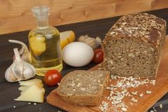 Freshly baked whole wheat bread. Preparing homemade breakfast. Various ingredients for the meal. Royalty Free Stock Photo