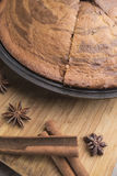 Freshly baked zebra pie, cinnamon sticks, anise stars lie on a light wooden background Royalty Free Stock Photo