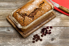 Freshly baked zucchini bread on rustic wooden boards. Freshly baked homemade zucchini bread in glass pan with knife and cloth napkin on rustic wood Royalty Free Stock Image