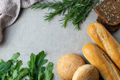 Freshly bakes bread, herbs and greens on a table, overhead flat lay stock photos
