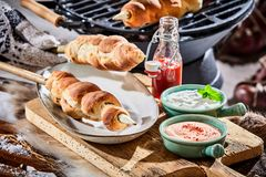 Freshly barbecued skewers of crusty twist bread. On a table outdoors in winter snow with bowls of dipping sauce and ketchup Royalty Free Stock Images