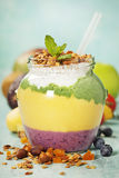 Freshly blended fruit smoothie in glass jar with straw. Turquoise blue background, copy space Royalty Free Stock Image