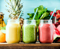 Freshly blended fruit smoothies of various colors and tastes. In glass jars. Yellow, red, green. Turquoise blue background stock photo