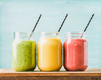 Freshly blended fruit smoothies of various colors and tastes. In glass jars. Yellow, red, green. Turquoise blue background royalty free stock image